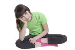 La niña que se pone en cuclillas a piernas cruzadas Fotografía de archivo