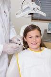 La niña que se sienta en dentistas preside la sonrisa en la cámara Fotografía de archivo