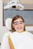 La niña que se sienta en dentistas preside los vidrios protectores que llevan Fotos de archivo