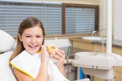 La niña que se sienta en dentistas preside sostener los dientes modelo Fotografía de archivo libre de regalías