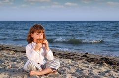 La niña que se sienta en la playa y la cacerola del juego instalan tubos Fotos de archivo libres de regalías