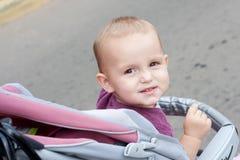 La niña que se sienta en un carro de los niños Foto de archivo