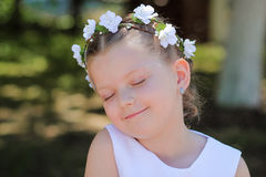 La niña que soñaba con los ojos se cerró, niño con una guirnalda de flores artificiales en su cabeza Foto de archivo libre de regalías