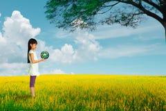 La niña que sostiene la tierra con recicla símbolo en el campo de flor Fotografía de archivo libre de regalías