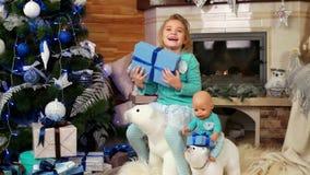 La niña que sostiene un regalo de la Navidad, niño no quiere ser regalo dividido, muchacha que juega cerca del árbol de navidad c metrajes