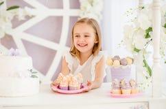 La niña que sostiene una placa rosada con el dulce se apelmaza en la barra de caramelo Fotografía de archivo