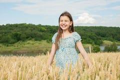 La niña ríe en el campo de trigo Imagen de archivo libre de regalías