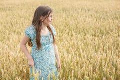 La niña ríe en el fondo del campo de trigo Imágenes de archivo libres de regalías