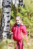La niña recoge la savia del abedul en bosque Imagen de archivo libre de regalías