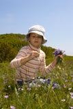 La niña recoge las flores Imágenes de archivo libres de regalías