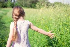 La niña recorre en el campo Foto de archivo