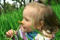 La niña recorre en el resorte en una hierba joven fotos de archivo