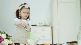 La niña revuelve la harina en un bol de vidrio almacen de video