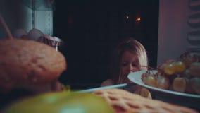 La niña saca la comida del refrigerador en la noche metrajes