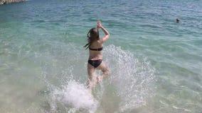 La niña salta en el mar almacen de video