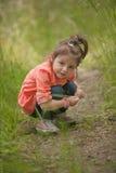 La niña se agachó en la hierba en el parque Imagen de archivo