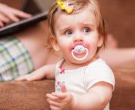 La niña se coloca cerca del sofá Imágenes de archivo libres de regalías