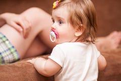 La niña se coloca cerca del sofá Imagen de archivo libre de regalías