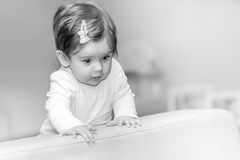 La niña se coloca cerca del sofá en casa Imagen de archivo