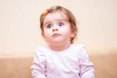 La niña se coloca cerca del sofá en casa Fotos de archivo libres de regalías