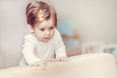 La niña se coloca cerca del sofá en casa Foto de archivo libre de regalías