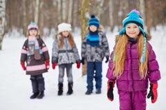 La niña se coloca en el parque del invierno, amigos se coloca detrás Imágenes de archivo libres de regalías