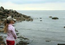 La niña se coloca en la playa Fotografía de archivo libre de regalías