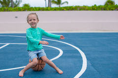 La niña se divierte con baloncesto en Foto de archivo