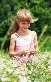La niña se está colocando en el prado Fotografía de archivo