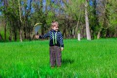 La niña se está colocando en la hierba verde con un paquete de flores fotos de archivo