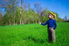 La niña se está colocando en una hierba verde en una guirnalda de flores Fotografía de archivo