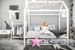 La niña se está sentando en la cama con su juguete Foto de archivo