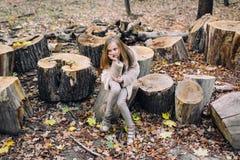 La niña se está sentando en tocón de madera en el bosque en el día del otoño Imágenes de archivo libres de regalías