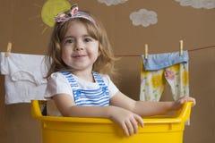 La niña se está sentando en un baño amarillo Imagenes de archivo
