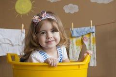 La niña se está sentando en un baño amarillo Fotos de archivo libres de regalías