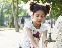 La niña se lava las manos en el golpecito Foto de archivo