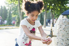 La niña se lava las manos en el golpecito Fotografía de archivo