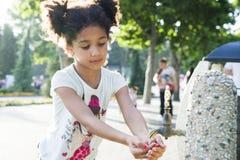 La niña se lava las manos en el golpecito Imagen de archivo libre de regalías