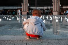 La niña se sienta al lado de la fuente, y de juegos con el agua imagen de archivo libre de regalías