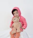 La niña se sienta con el oso de peluche fotografía de archivo
