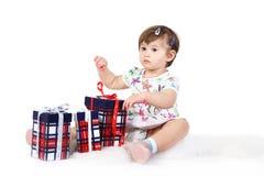 La niña se sienta con tres rectángulos de regalo Foto de archivo libre de regalías