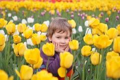 La niña se sienta en el campo de tulipanes Imagenes de archivo