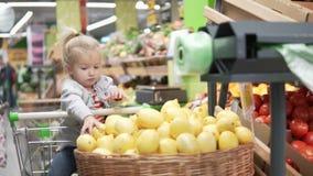 La niña se sienta en el carro del ultramarinos en el supermercado almacen de metraje de vídeo