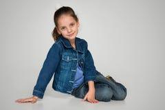 La niña se sienta en el fondo gris Imagenes de archivo