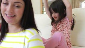 La niña se sienta en el sofá almacen de metraje de vídeo