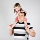 La niña se sienta en hombros del padre y mira abajo Foto de archivo