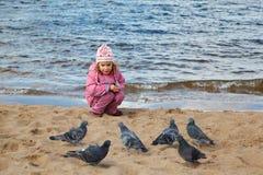 La niña se sienta en la playa en el borde del agua en otoño Foto de archivo