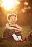La niña se sienta en puesta del sol Imágenes de archivo libres de regalías