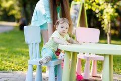 La niña se sienta en silla en parque Foto de archivo