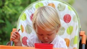 La niña se sienta en silla y come el mango y ríe almacen de video